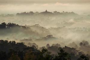 Colorful sunrise over Borobudur temple in misty jungle forest, I