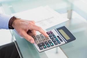 Businessman pushing key on calculator photo