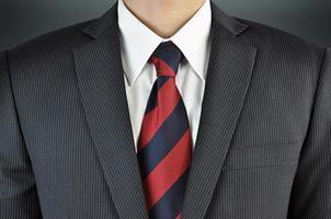 Man wearing suit with stripe necktie - business attire photo