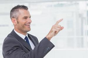 empresario alegre señalando mientras mira lejos