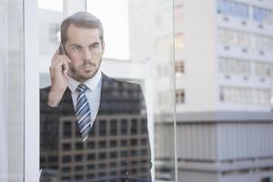 uomo d'affari guardando fuori dalla finestra al telefono