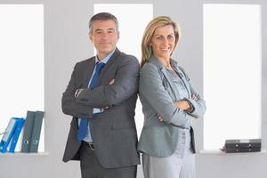 Two smiling businesspeople looking  standing back-to-back photo