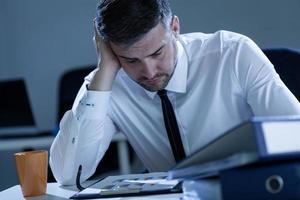 uomo che lavora fino a tardi in ufficio