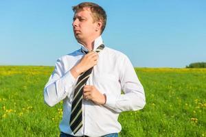 man in white shirt straightens his tie