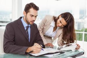 empresario y secretaria mirando el diario en la oficina foto