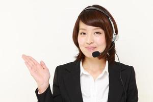 mulher de negócios japonesa do call center, apresentando e mostrando algo