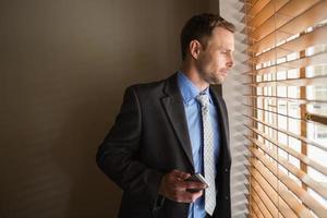 hombre mirando a través de las persianas mientras sostiene su teléfono foto