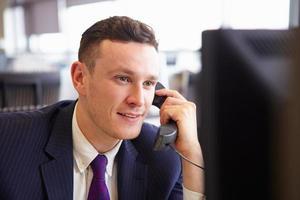 cabeça e ombros de um jovem empresário, usando telefone