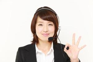 femme d'affaires japonaise de centre d'appels montrant un signe de victoire