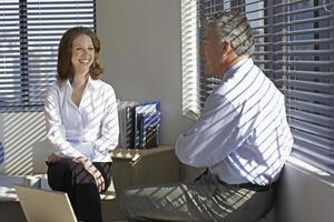 Two Businesspeople Talking by Window photo