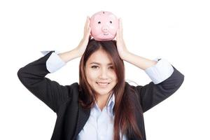 Young Asian businesswoman hold  piggy bank over head