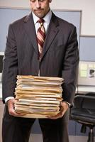Businessman Carrying Stack of File Folders photo