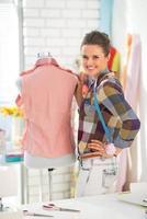 Retrato de costurera feliz con maniquí foto