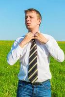 Portrait of a businessman, straightens his tie in field
