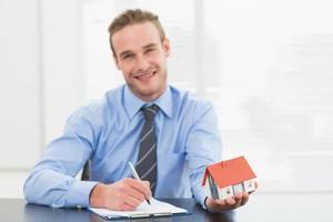 empresário, anotando e mostrando a casa em miniatura