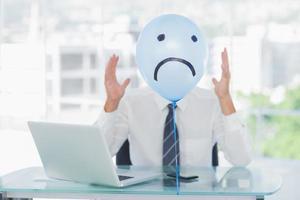 Blue balloon hiding angry businessmans face