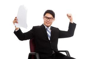 Aziatische zakenman zit op bureaustoel blij met succes