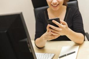 Smiling Young Woman Using Her Smart Phone in the Office photo