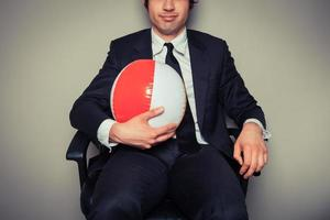 Businessman with beach ball in office chair