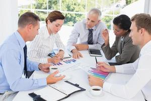Business team analyzing bar chart graphs photo