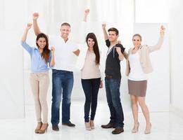 empresários confiantes em pé com os braços levantados