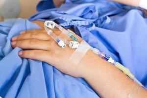 paciente de mano con un goteo intravenoso foto