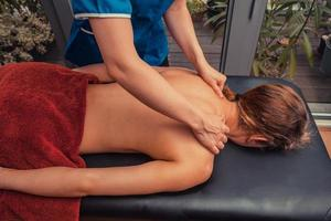 Massage therapist treating patient at home photo