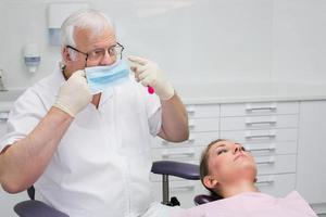 tandarts zet een beschermend masker