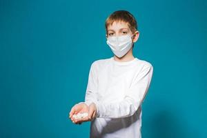 Boy in white protection mask holding pills photo