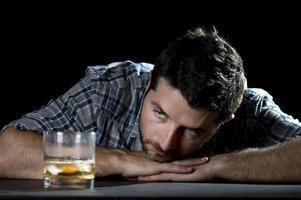 Hombre alcohólico borracho con vaso de whisky en concepto de alcoholismo