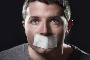 atractivo joven boca sellada en cinta adhesiva foto