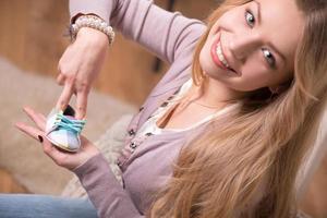 mujer atractiva joven que sostiene el zapato de bebé, tiro interior foto