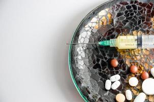 jeringa y pastillas en un plato