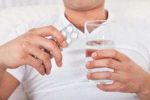 uomo con confezione di pillole e bicchiere d'acqua