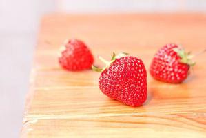 Three strawberries on table, side view