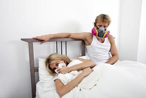 Man wearing gas mask while woman suffering from cold