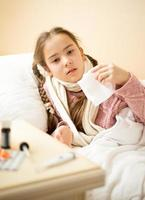 ziek meisje dat in bed ligt en papieren zakdoekje houdt
