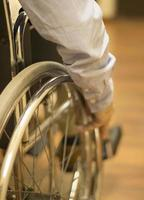 Man in wheel chair in hospital clinic closeup on wheel photo