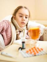 Chica con gripe acostada y mirando la taza de té foto