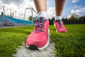 photo of pink female sneakers on soccer grass field