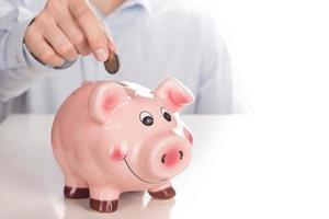 Man's hand putting coin into piggy bank