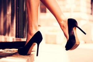 Primer plano de mujer con tacones negros equilibrado en un escalón foto