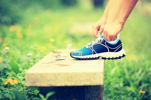 atar cordones de los zapatos en el banco de piedra en la hierba verde foto