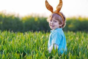 lindo niño con orejas de conejo de pascua en la hierba verde