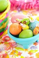 colored Easter eggs and candy in blue bowl