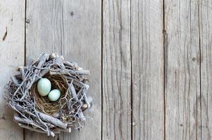 Easter eggs in nest on wood