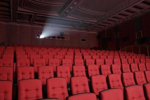 Empty cinema with red seats and detailed ceiling