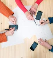 Close-up top view of businesspeople hands with pens papers smartphones. photo