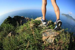 gambe della viandante della donna che fanno un'escursione sul picco di montagna della spiaggia