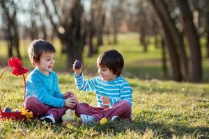 dos muchachos en el parque, divirtiéndose con huevos de colores